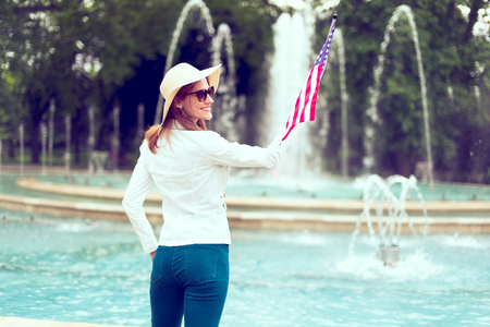 Patriot woman in hat holding USA flag in park at fountain, rear view, Independence day, 4th of July, vintage style Фото со стока