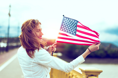Happy young patriot urban woman with toothy smile stretching USA flag, profile view, with sunlight