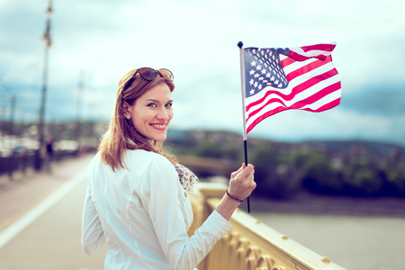 Happy young patriot modern urban woman waving USA flag portrait
