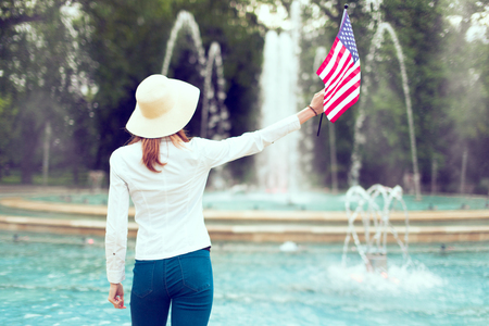Elegant patriot woman in hat holding USA flag in park rear view
