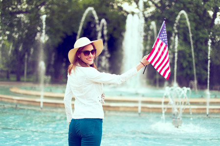 Patriot woman in hat holding USA flag in park rear view, looking back, toothy smile, Independence day, 4th of July, vintage style Фото со стока