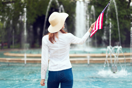 Stylish patriot woman in hat holding USA flag in park rear view, Independence day, 4th of July
