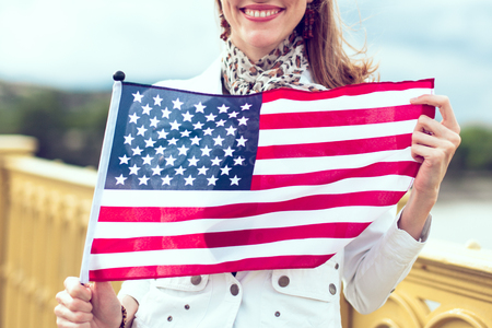 Happy young patriot urban woman with toothy smile stretching USA flag concept