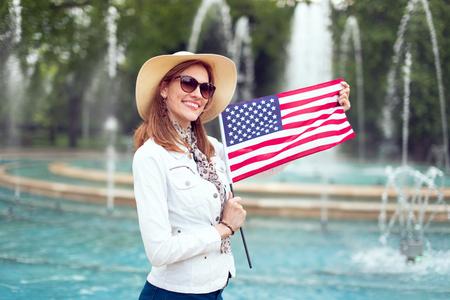 Young fashionable excited woman holding USA flag in park at fountain, Independence day, Fourth of July Фото со стока