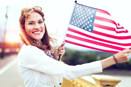 Happy young patriot urban woman with toothy smile stretching USA flag in sunset
