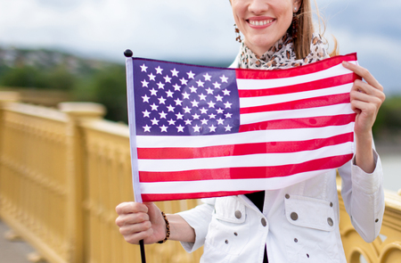 Happy young caucasian patriot urban woman with toothy smile stretching USA flag