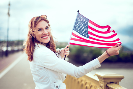 Happy young patriot urban woman smiling stretching USA flag