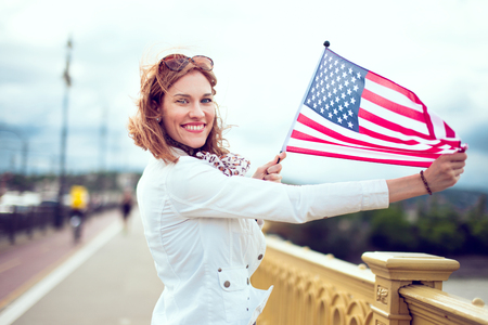 Happy young patriot urban woman with toothy smile enjoying stretching USA flag Фото со стока