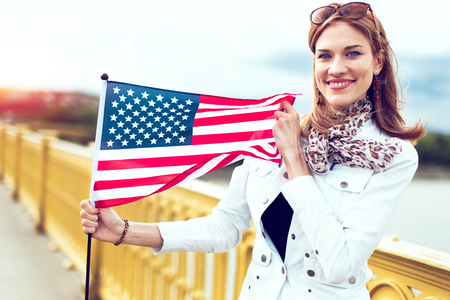 Happy young fashionable patriot urban woman in sunset with toothy smile stretching USA flag