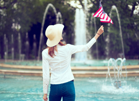 Patriot woman in hat holding USA flag in park rear view, looking up, Independence day, 4th of July Фото со стока