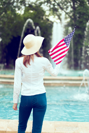 Patriot woman in hat holding USA flag in park rear view Фото со стока