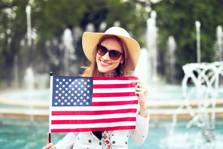 Happy young patriot urban woman in hat stretching USA flag in park, 4th of July, Indendence day