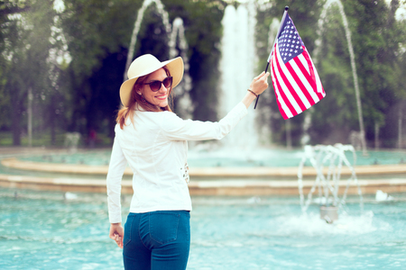 Patriot woman in hat holding USA flag in park rear view, looking back, toothy smile, Independence day, 4th of July Фото со стока