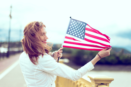 Happy young patriot urban woman with toothy smile stretching USA flag, profile view