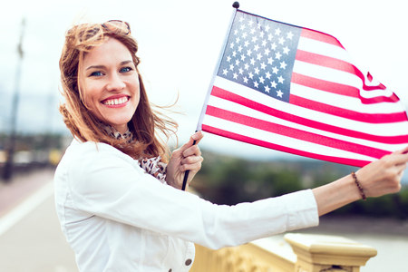 Happy young patriot urban woman with toothy smile stretching star spangled banner Фото со стока