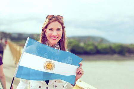Glückliche junge Frau, die Flagge von Argentinien mit einem zahnigen Lächeln hält, im Freien, Farbe abgestuft Standard-Bild