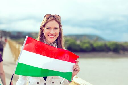 Happy young woman holding flag of Hungary with toothy smile, outdoors, color graded