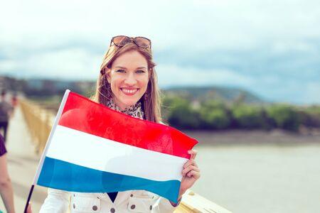 Glückliche junge Frau, die niederländische Flagge mit einem zahnigen Lächeln hält, im Freien, Farbe abgestuft