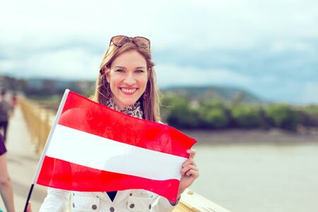 Happy young woman holding flag of Austria with toothy smile, outdoors, color graded