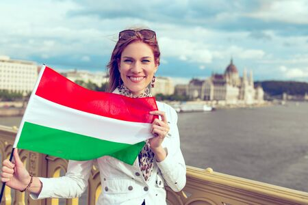 Happy young woman with toothy smile stretching Hungarian flag on Margaret bridge, near to Parliament building, In cinematic style outdoors, Budapest, Hungary 版權商用圖片