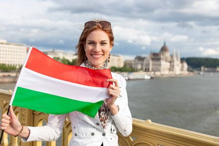 Happy young woman with toothy smile stretching Hungarian flag on Margaret bridge, near to Parliament building, outdoors, Budapest, Hungary