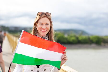 Happy young natural beauty woman holding flag of Hungary with toothy smile, outdoors in city, Budapest, Hungary Фото со стока
