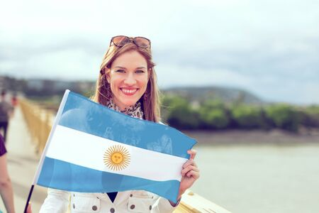 Happy young beautiful woman holding flag of Argentina with toothy smile, outdoors