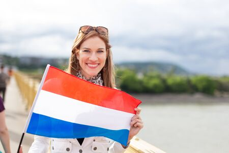 Happy young woman holding Dutch flag with toothy smile, outdoors Фото со стока
