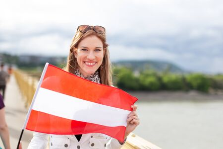 Happy young natural woman holding flag of Austria with toothy smile outdoors Фото со стока