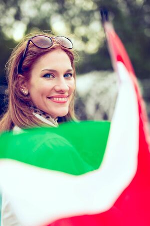 Happy young woman with smile holding Hungarian flag, depth of field