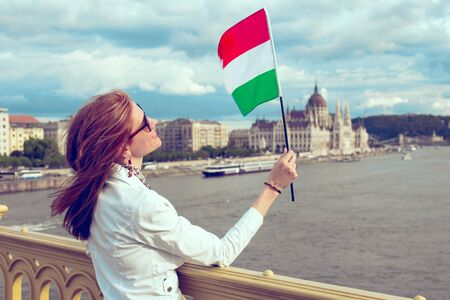 Happy young woman looking up onto Hungarian flag at Budapest panorama, Hungary Фото со стока