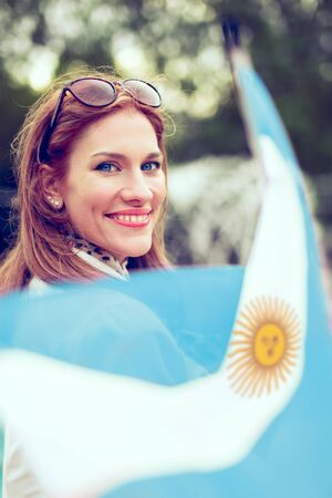 Happy young woman with smile holding flag of Argentina in park Фото со стока