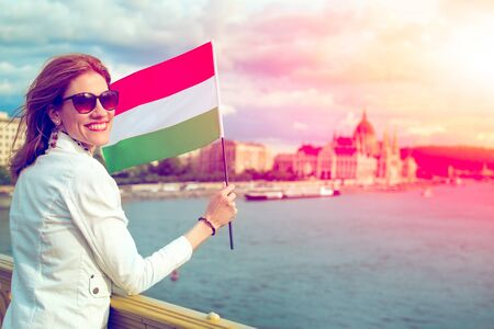 Happy young woman holding Hungarian flag at Budapest in sunset, Hungary Фото со стока