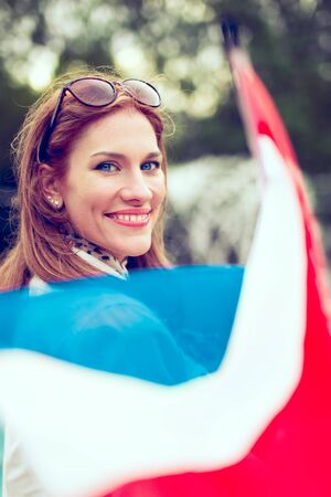 Happy young woman with smile holding flag of Netherlands in park, depth of field