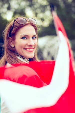 Happy young woman with smile holding flag of Austria in park