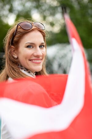 Happy young natural woman with smile holding flag of Austria park