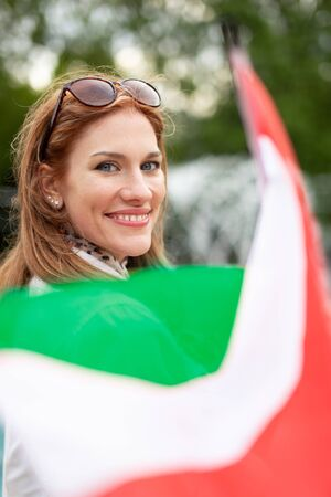 Happy young natural woman with smile holding Hungarian flag, depth of field