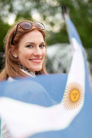 Happy young natural woman holding flag of Argentina in park, depth of field