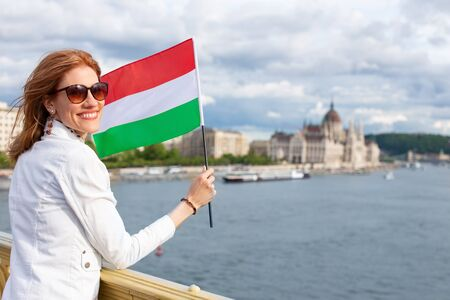 Happy young woman holding Hungarian flag at Budapest, Hungary Фото со стока