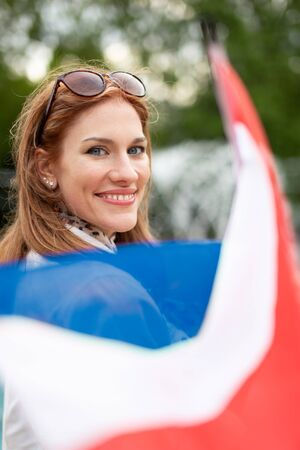 Happy young natural woman with smile holding flag of Netherlands in park, depth of field Stockfoto