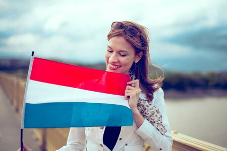 Happy young woman watching and holding Dutch flag, outdoors