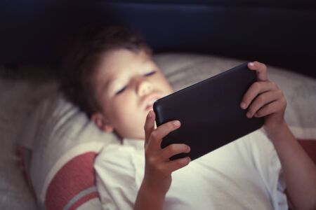 Little boy using digital tablet at night in bedroom