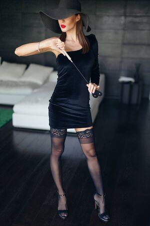 Sexy mujer dominante con sombrero y labios rojos posando con látigo en el interior