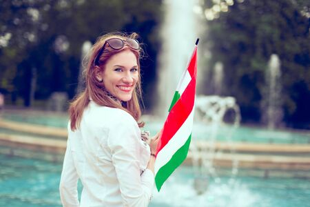 Happy young woman holding Hungarian flag at fountain, looking back, Margaret Island, Budapest, Hungary 版權商用圖片