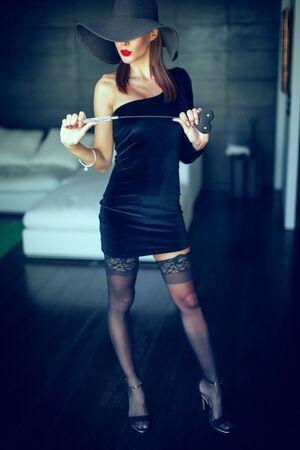 Leidenschaftliche dominante Femme Fatale in Hut mit Peitsche posiert in Luxushotel, Ganzkörper