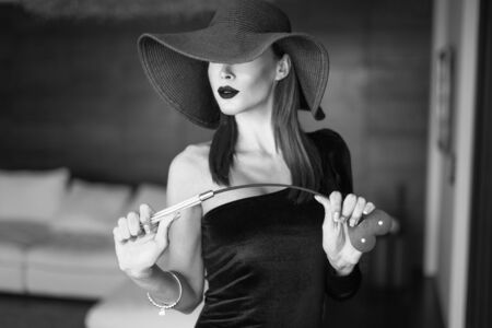 Passionate dominant femme fatale in hat with whip posing in luxury hotel, portrait, black and white