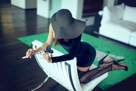 Sexy dominant femme fatale in hat holding whip on sofa, covering face and kneeling