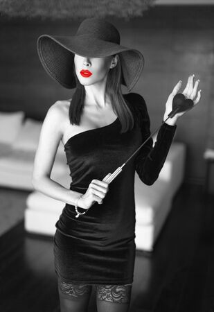 Passionate dominant femme fatale in hat with whip posing in luxury hotel, black and white selective coloring with red lips Stock fotó
