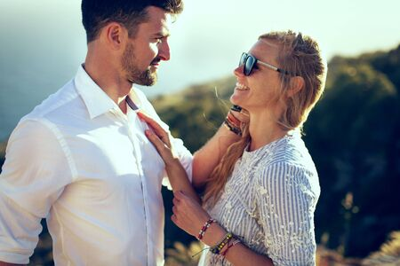 Happy young stylish couple in nature at summer touching each other portrait