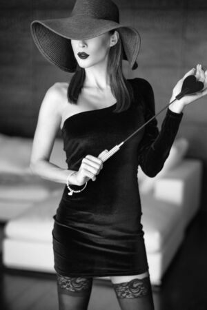 Passionate dominant femme fatale in hat holding whip posing in luxury hotel, black and white